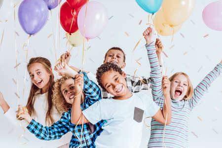 Groep gelukkige kinderen lachen, plezier hebben en ballonnen houden