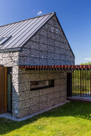 fense: Modern stone house in the suburbs with a garden