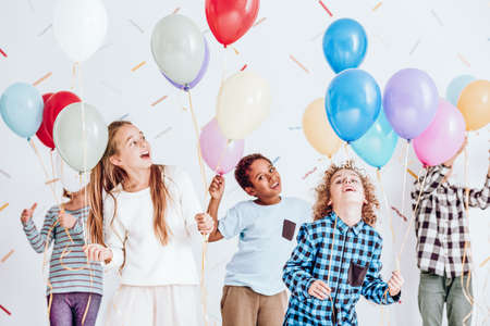 Groep van kinderen hebben een feest en dansen met ballonnen in hun handen Stockfoto