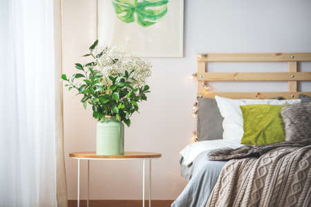 kingsize: Bunch of flowers on small table next to bed in cozy bright bedroom