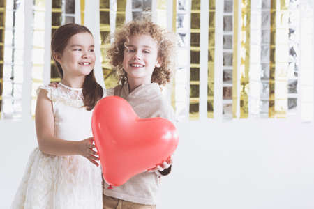 Small boy and girl holding red, balloon heart