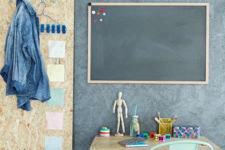 Modern room with blackboard, desk and grey and osb wall Stock Photo