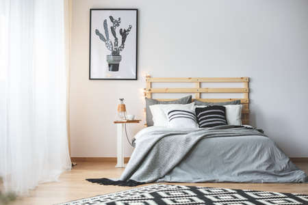 Black and white bedroom with grey accessories, big window and cactus poster Banque d'images