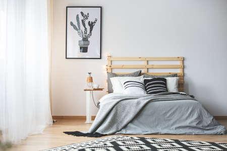 Zwart-witte slaapkamer met grijze accessoires, groot raam en cactus poster