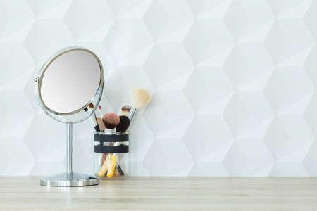 木製の机の上の小さな鏡と化粧ブラシ 写真素材