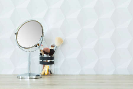 Small mirror and makeup brushes on wooden desk