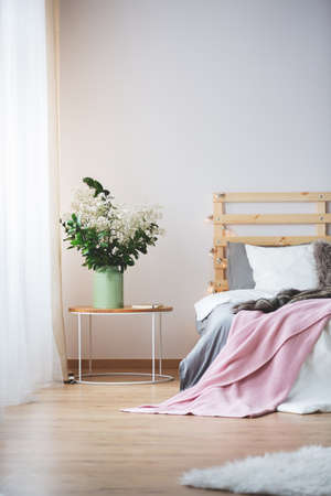 kingsize: Modern bed and small nightstand with bunch of flowers in cozy bedroom