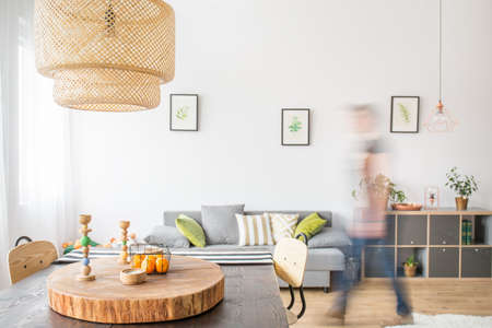 ceiling slab: Functional apartment with wood dining table, ceiling lamp and sofa