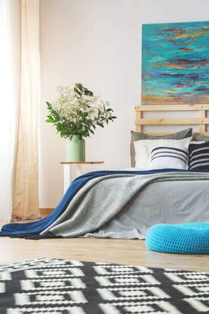 #75270927   Geräumiges Modernes Schlafzimmer Mit Großem Bett, Blauer Malerei  Und Blumen