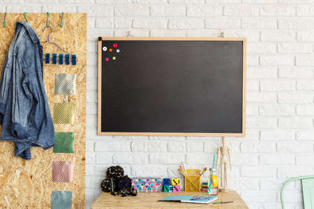 Desk with accessories and mockup blackboard on a white brick wall