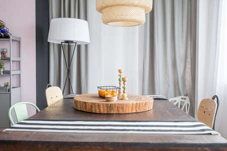 ceiling slab: Room with table, round wood slab and ceiling lamp
