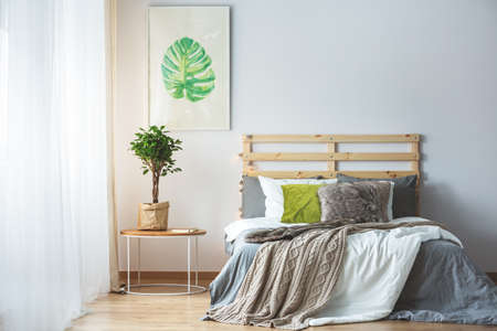 Pastel bedroom interior with green accessories and monstera poster