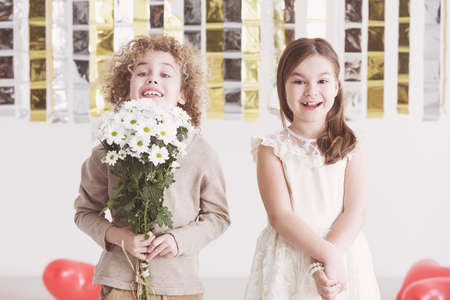 Small boy holding bouquet of flowers and cute girl next to him Stock Photo