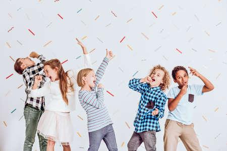 Grupo de niños y niñas felices pretendiendo cantar en una fiesta Foto de archivo