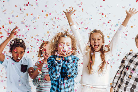 Happy kids having fun in a room full of confetti