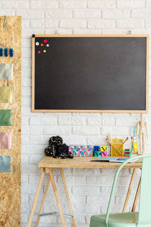Modern room with blackboard on a brick wall and desk with accessories