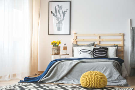 Trendy bedroom interior with king-size bed, pouf, flowers and cactus poster