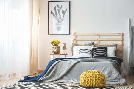 Trendy slaapkamerinterieur met king-size bed, poef, bloemen en cactusaffiche Stockfoto