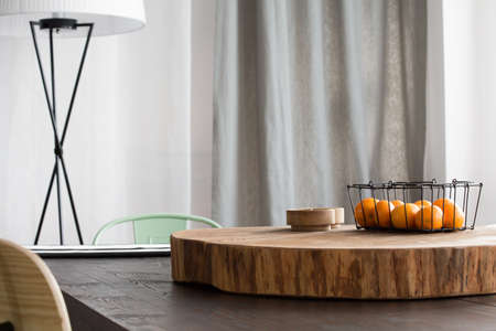ceiling slab: Dining room with round wooden desk on table and lamp Stock Photo