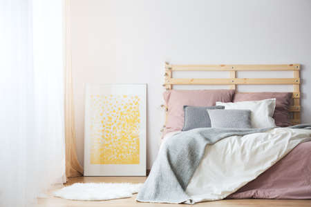 kingsize: King-size bed, yellow poster and white rug in cozy bedroom