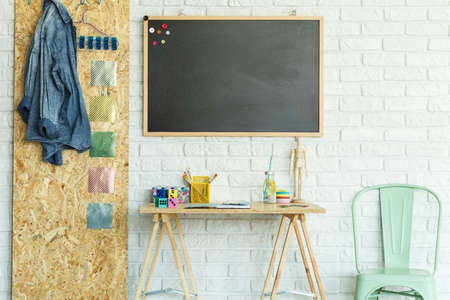 Desk, blackboard with magnets, chair and osb board in modern room Stock Photo