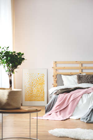 Plant and yellow poster in cozy modern bedroom