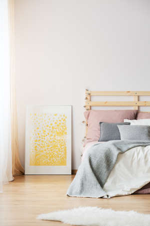 Yellow poster next to bed in cozy bedroom