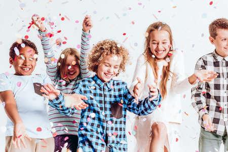 Gelukkige kinderen gooien kleurrijke confetti in een kamer Stockfoto