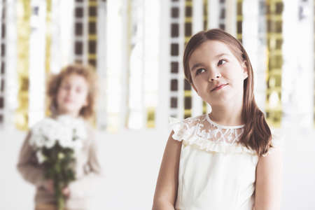 careless: Pensive, small girl with heart dilemma, boy in background Stock Photo