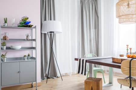 ceiling slab: Room with grey window curtain, metal bookcase and wood table