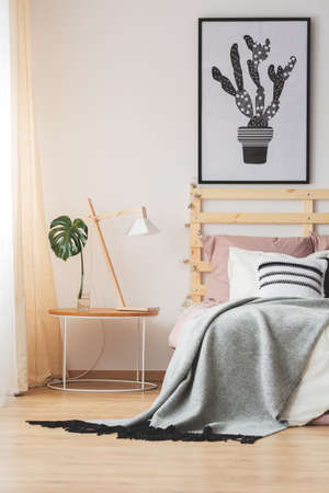 poster bed: Creative modern bedroom design with cactus poster and nightstand with lamp and monstera