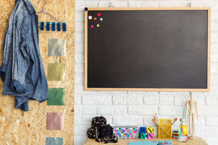 Creative room design with blackboard and desk with accessories Banco de Imagens