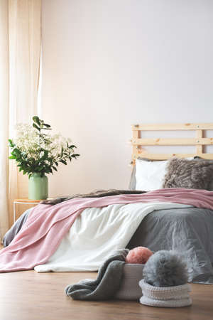 kingsize: King-size bed in modern bedroom interior with flowers on nightstand Stock Photo