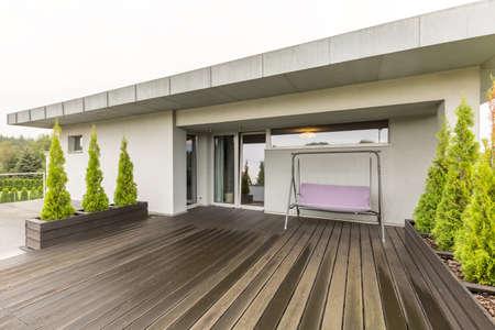 case moderne: Ampia terrazza in legno con altalena con veranda e piante in vaso