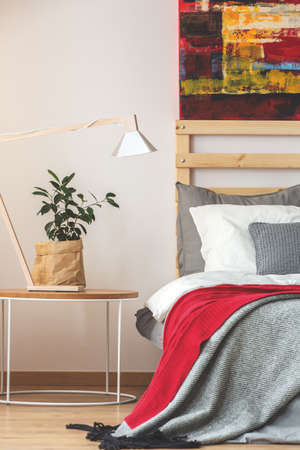 kingsize: Creative trendy bedroom with plant and lamp on small table and painting above the bed