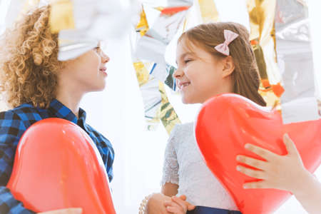 Cute child couple with red hearts celebrating valentines day
