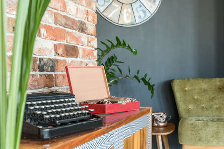 Black typewriter on a cabinet in old-school living room Stock Photo