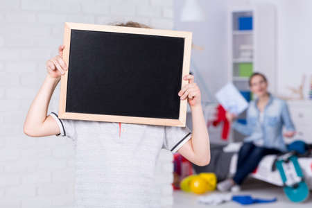 Boy covering face by blackboard with his mother behind