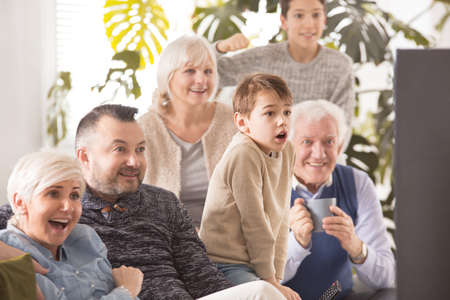 Excited family cheering in front of tv