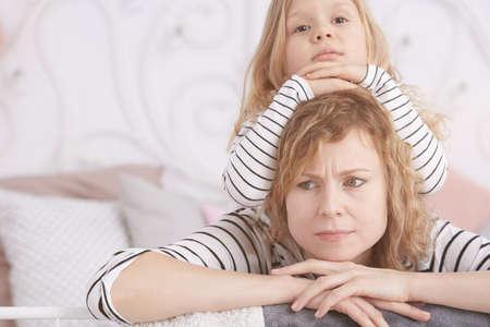 Kleines Mädchen legte auf ihre wütende Mutter auf ein Bett Standard-Bild - 75683507