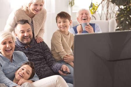 多世代家族一緒にテレビを見ながら笑いを愛する 写真素材