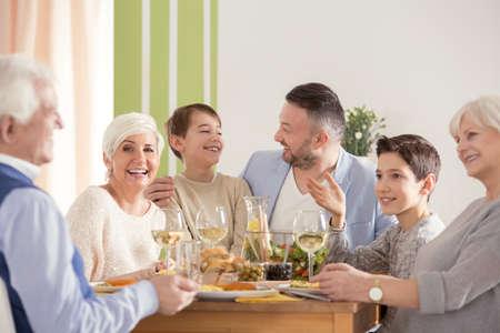 Family eating easter dinner, sitting together beside table