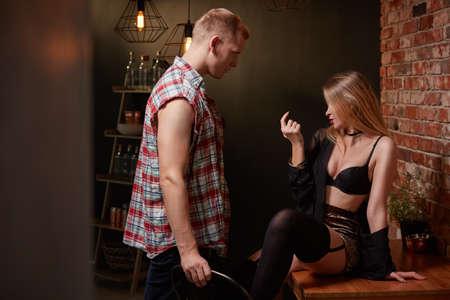 Sexy Dame, die auf Tabelle, gutaussehender Mann verführend sitzt Standard-Bild - 75717937