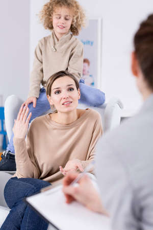 pedagogical: Boy sitting behind mother in therapist room