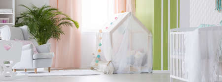 Boho style baby room with white cot and house bed