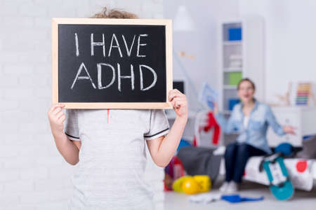Boy holding blackboard and admitting suffering from ADHD 版權商用圖片