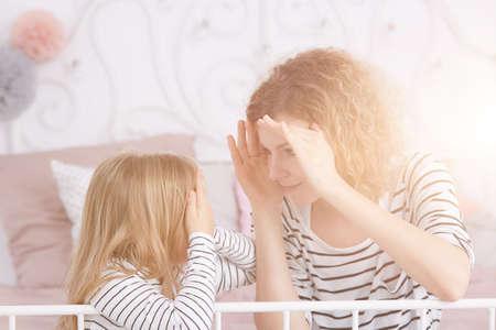 Junge Frau, die mit einem kleinen Mädchen im gemütlichen Schlafzimmer spielt Standard-Bild - 75718011