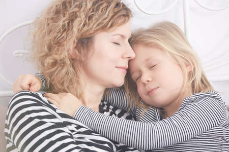 Little blonde girl hugging her mom while sleeping on a bed