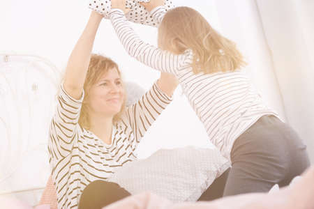 Mom and daughter having pillowfight on a bed in cozy bedroom