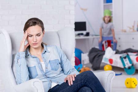 Vrouw met hoofdpijn zitten op leunstoel in rommelige kamer